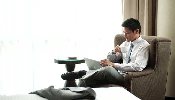 Businessman on laptop and drinking coffee