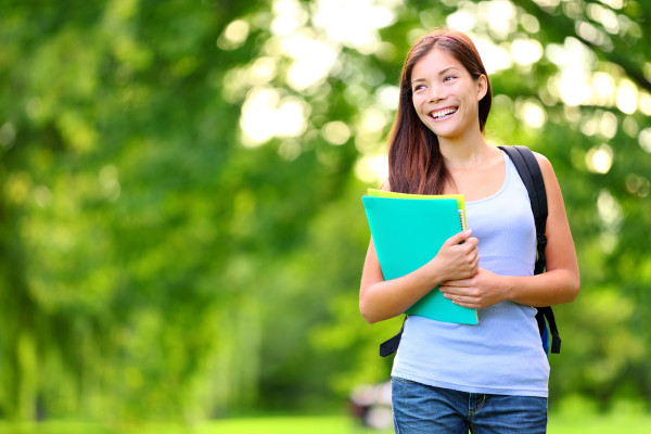 Student girl outdoor in park smiling happy going back to school.