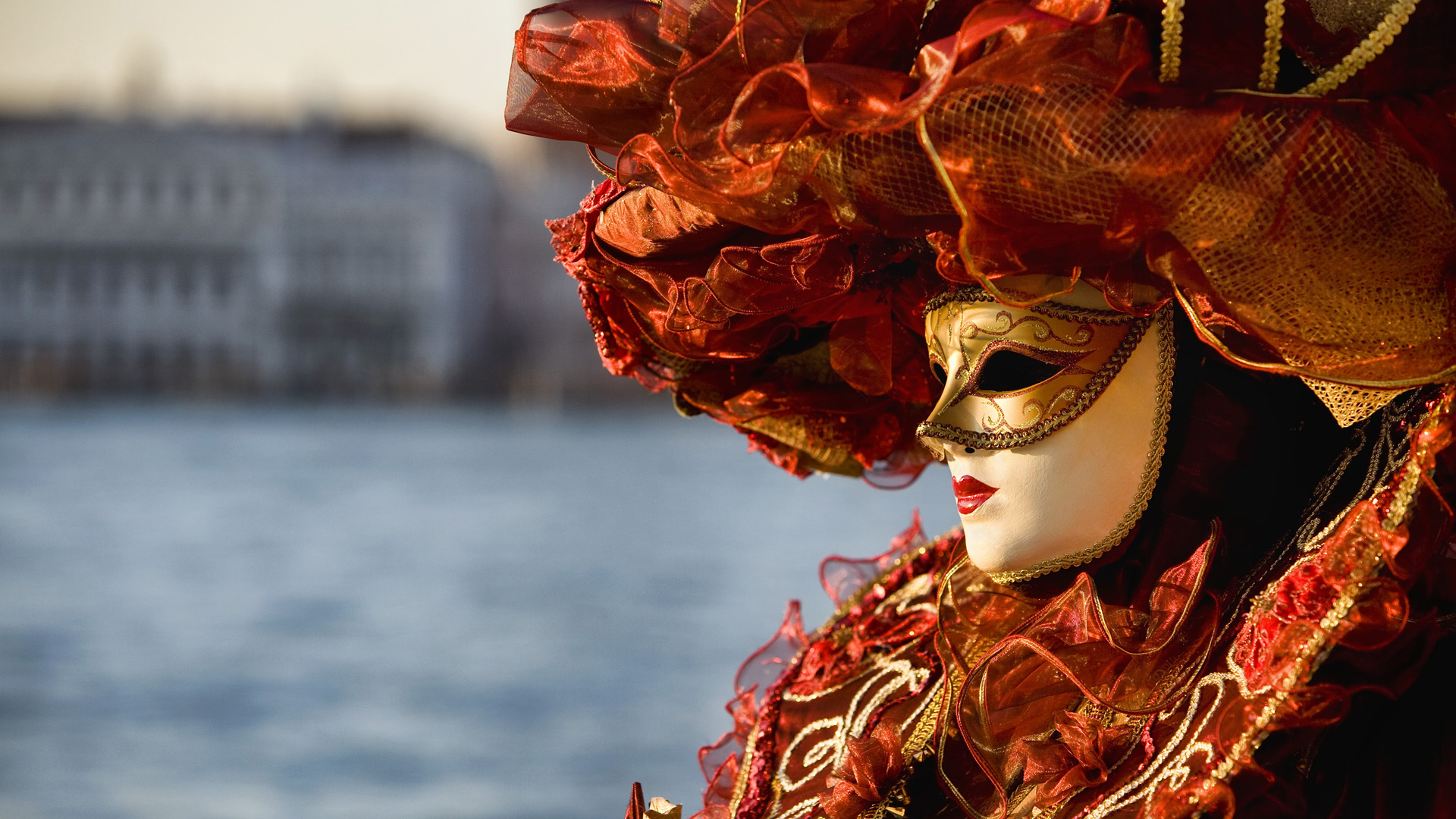 Woman wearing Carnival mask and costume by water