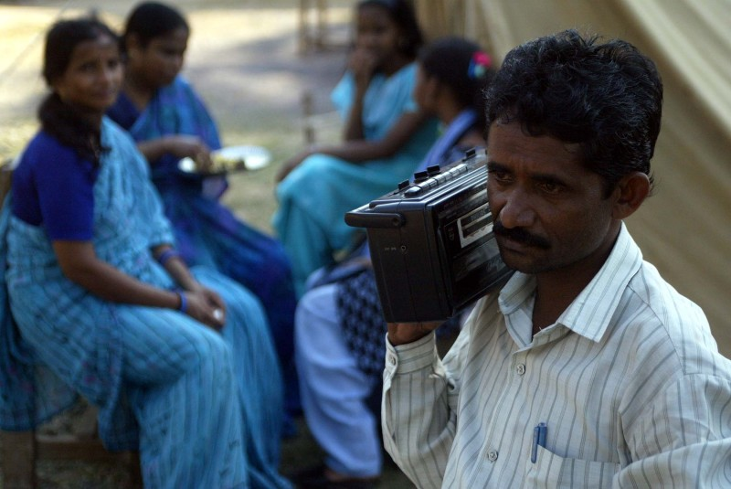 An Indian man and listens radio news inside a relief camp in Port Blair.