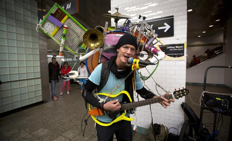 One-man band musician Jeffrey Masin performs at the Times Square subway station for tips in New York