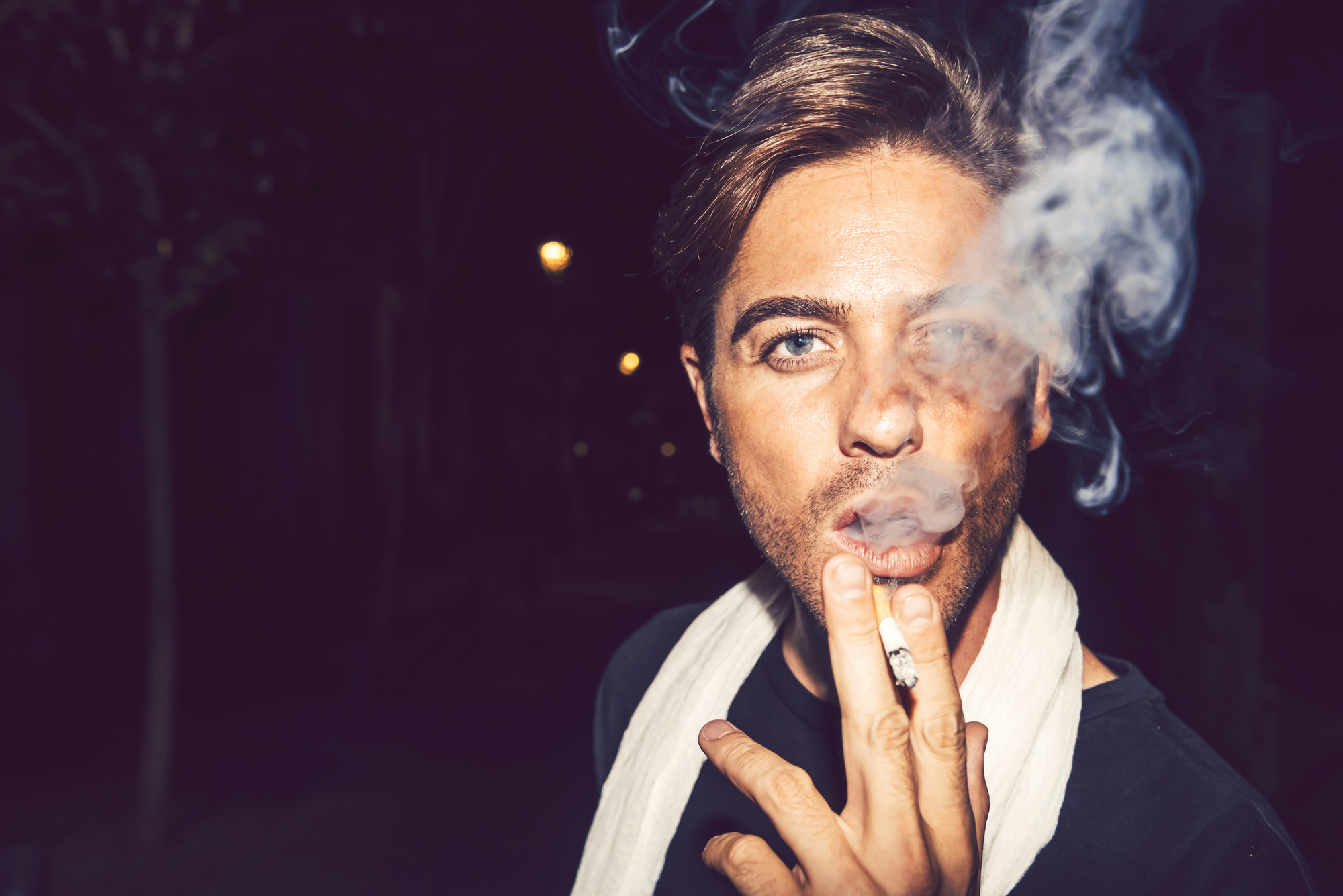 Young fashion man smoking a cigarette on the night street