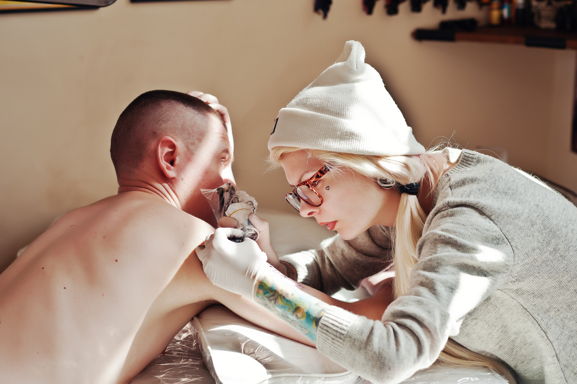 Young blonde woman master tattooist in glasses and hat with tatt
