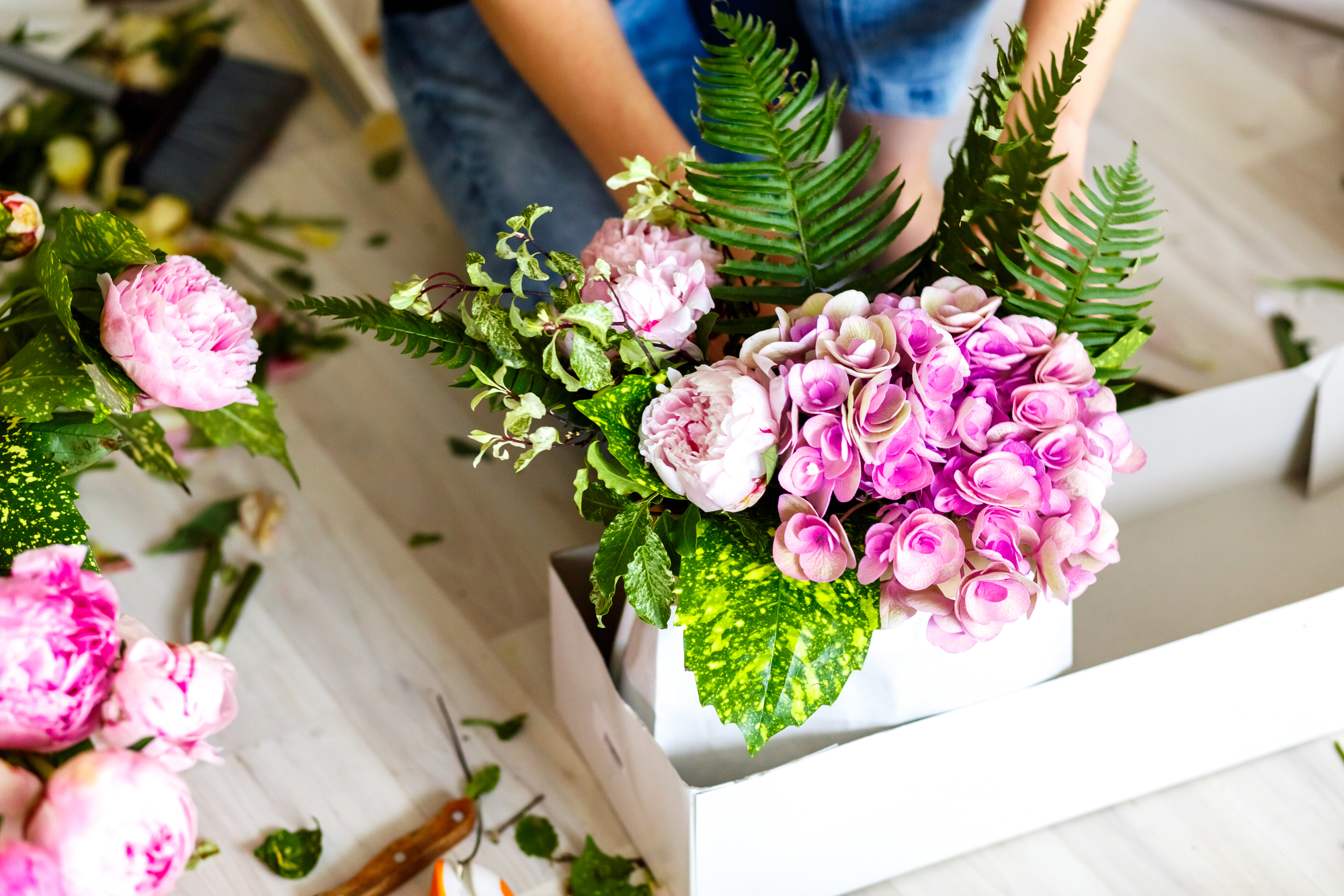 Florist making a bouguet of peonies