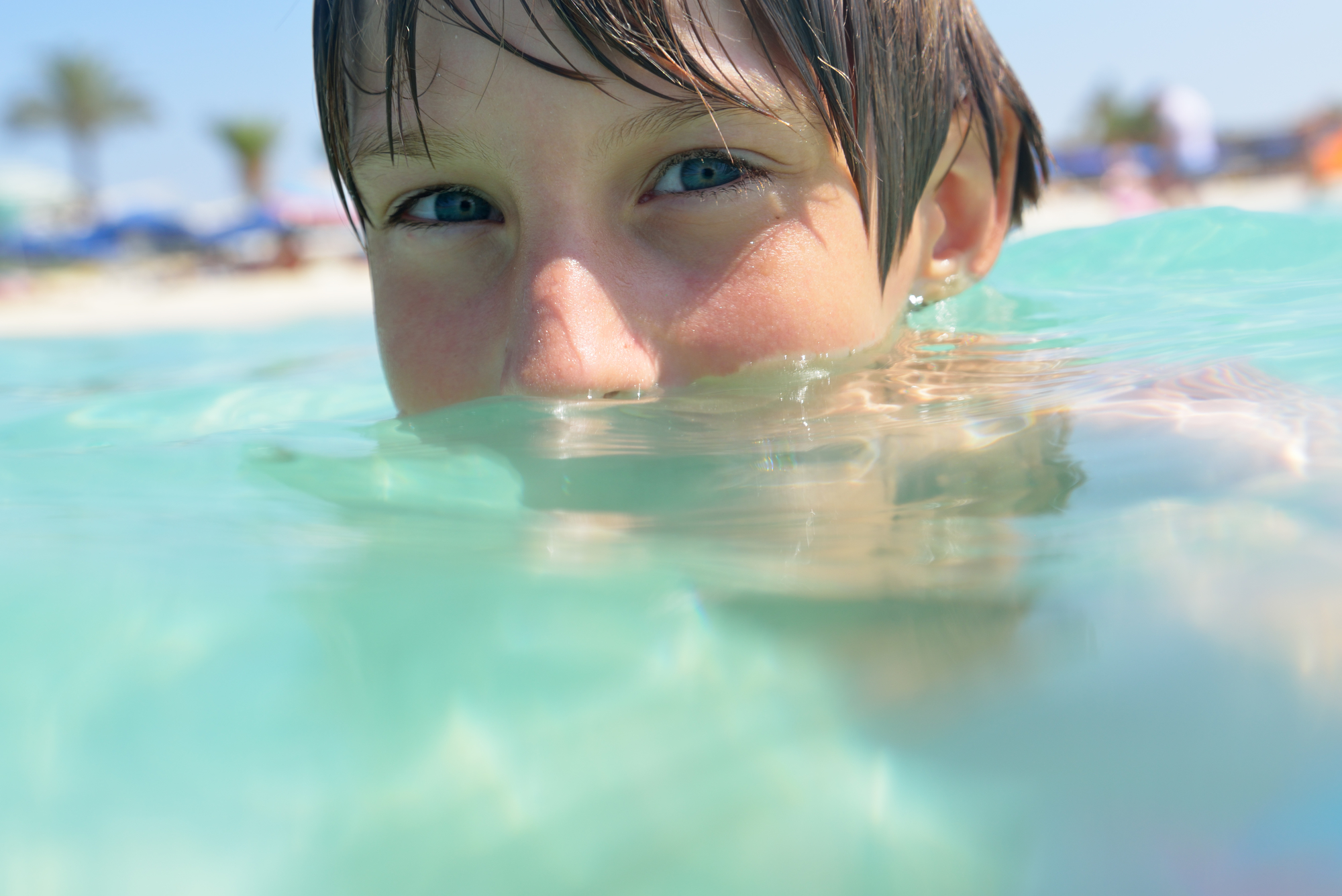 little boy swimming in sea with clean turquoise water transparen